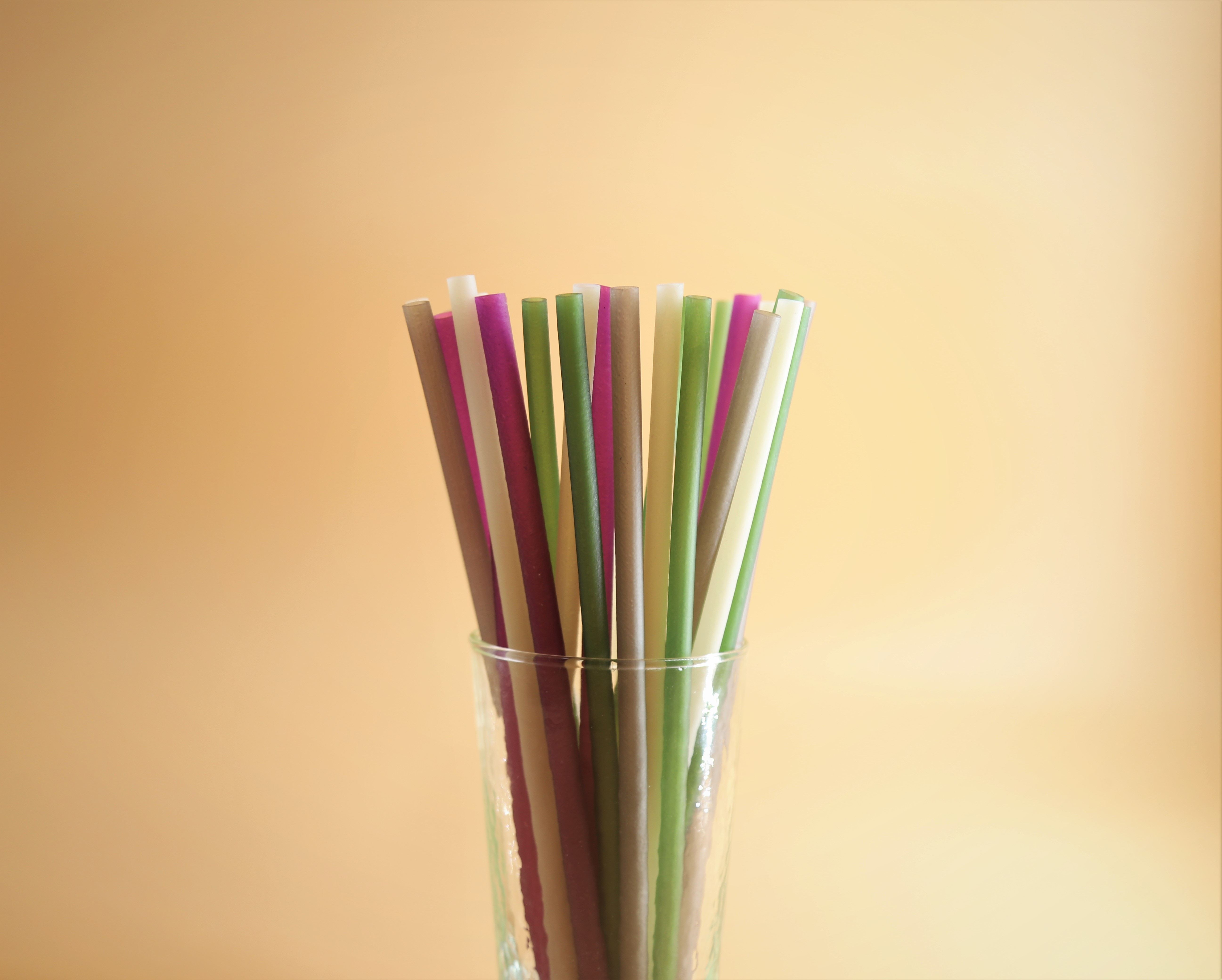 Colorful straws in a cup with a light yellow background