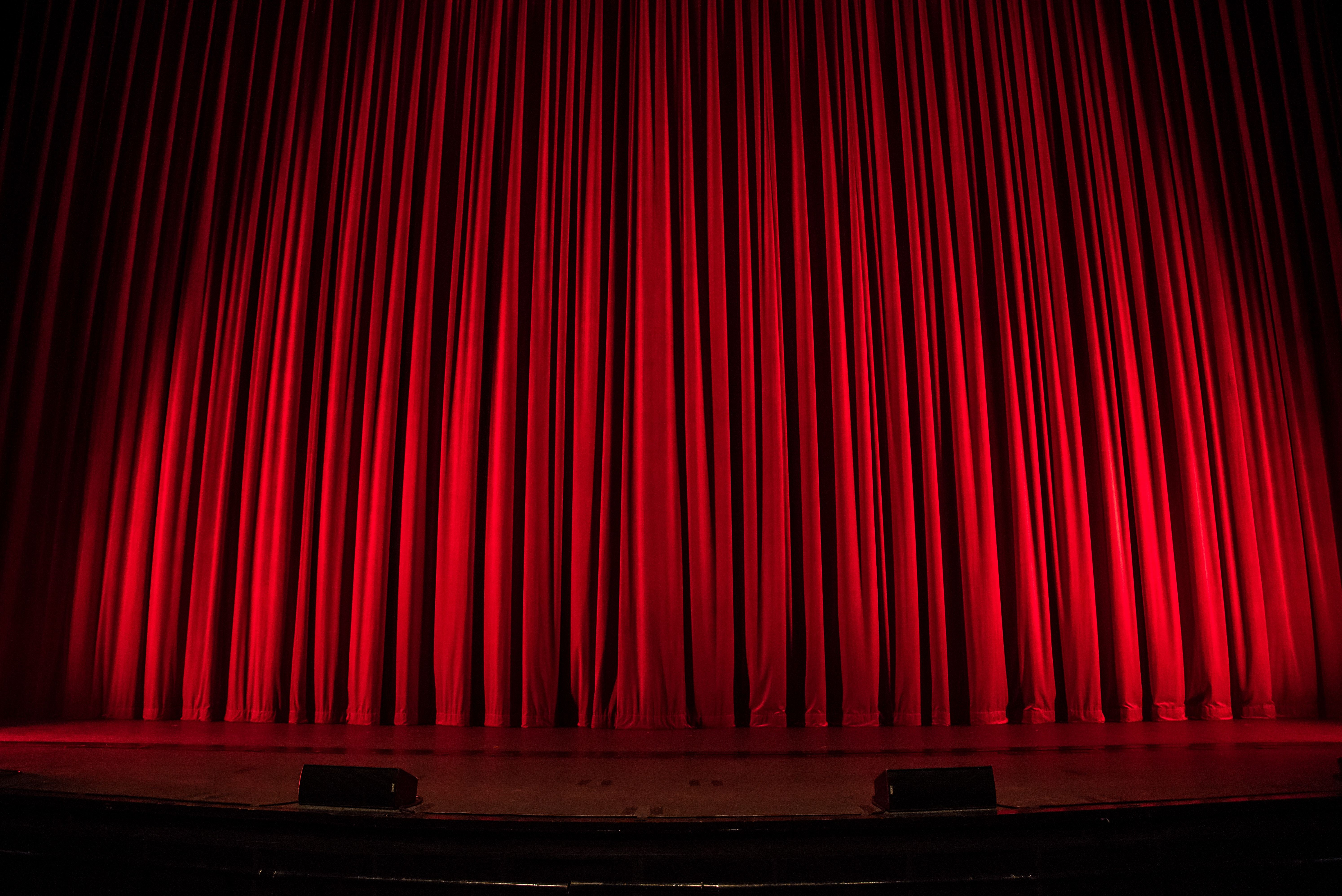 theater stage with red curtains drawn shut